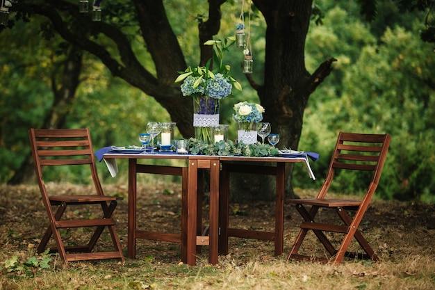 Na drewnianym stole w lesie znajduje się kompozycja kwiatów