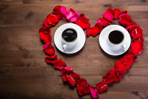 Na drewnianym stole, w środku płatków róż, znajdują się dwie filiżanki kawy