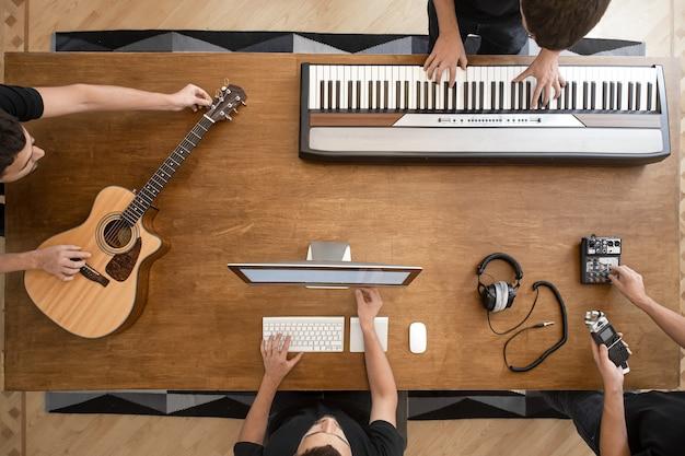 Na drewnianym stole w studiu nagrań, klawiatura muzyczna, gitara akustyczna, mikser i komputer.