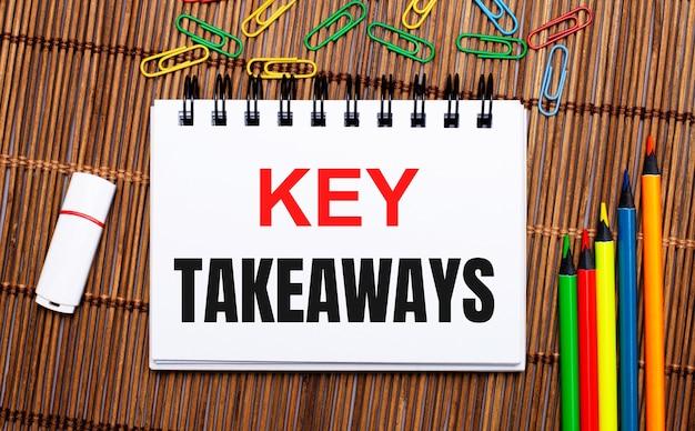 Na drewnianym stole wielokolorowe ołówki, spinacze, biały pendrive i notes z napisem key takeaways. płaskie ułożenie