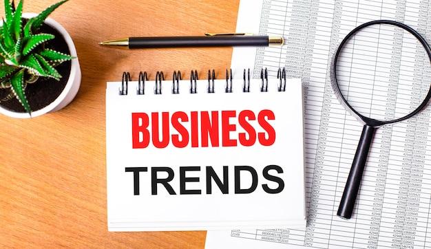 Na drewnianym stole znajdują się reportaże, roślina doniczkowa, lupa, czarny długopis i zeszyt z napisem business trends. pomysł na biznes