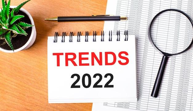 Na drewnianym stole znajdują się reportaże, roślina doniczkowa, szkło powiększające, czarny długopis oraz zeszyt z napisem trendy 2022. koncepcja biznesowa