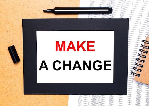 Na drewnianym stole znajduje się czarny otwarty marker, brązowy notatnik i kartka w czarnej ramce z napisem zmień zmianę