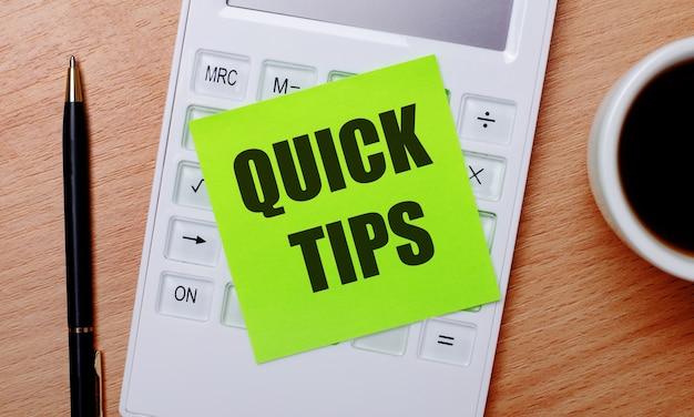 Na drewnianym stole znajduje się kawa w białej filiżance, długopis oraz biały kalkulator z zieloną naklejką z napisem quick tips. pomysł na biznes