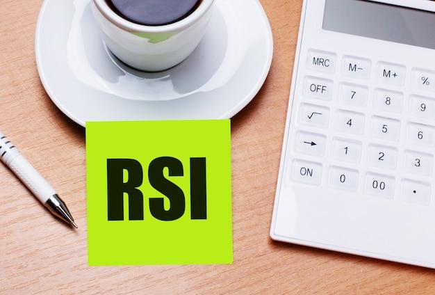 Na drewnianym stoliku znajduje się biała filiżanka kawy, długopis, biały kalkulator oraz zielona naklejka z napisem rsi relative strength index. pomysł na biznes