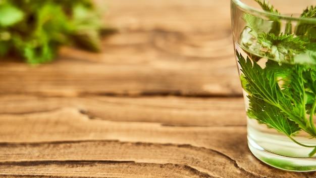 Na drewnianym tle jest szklanka z warzonymi młodymi pokrzywami