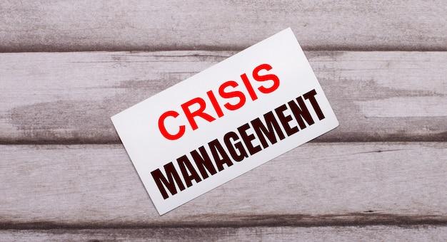 Na drewnianym tle znajduje się biała kartka z czerwonym napisem zarządzanie kryzysowe