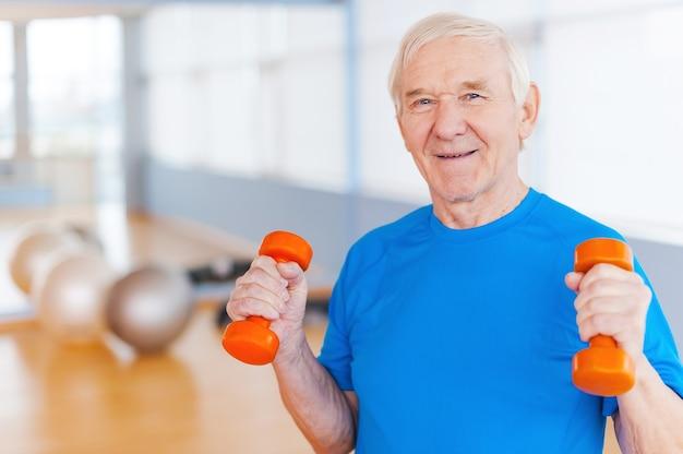 Na drodze do wyzdrowienia. szczęśliwy starszy mężczyzna ćwiczący z hantlami i uśmiechający się stojąc w pomieszczeniu