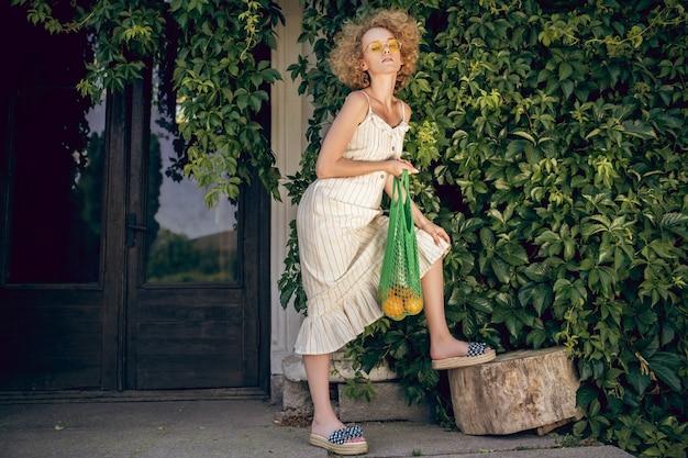 Na dworze. śliczna kobieta w okularach przeciwsłonecznych na tle zieleni