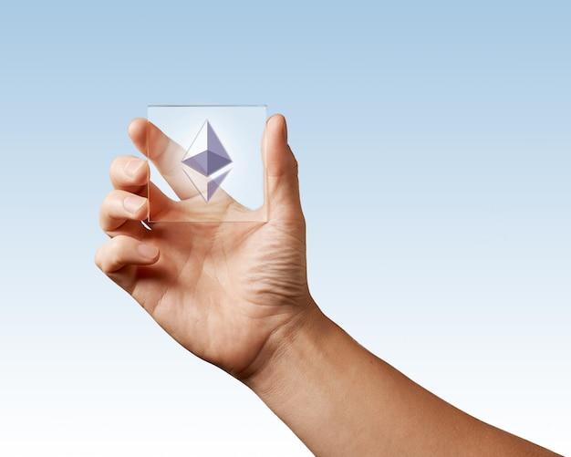 Na ekranie cyfrowym ikona ethereum mężczyzna trzyma w dłoni na niebieskiej powierzchni. obraz koncepcyjny dla rynku kryptowalut, technologii i kryptowaluty
