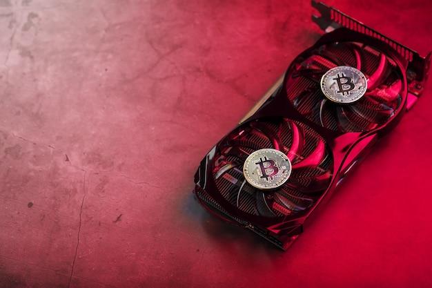 Na fanach potężnej karty graficznej wyświetlane są monety kryptowaluty bitcoin z czerwonym podświetleniem.koncepcja kopania i wydobywania kryptowaluty to farma kryptowalut.