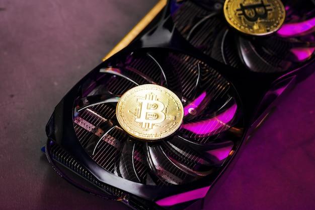 Na fanach potężnej karty graficznej wyświetlane są monety kryptowaluty bitcoin z czerwonym podświetleniem