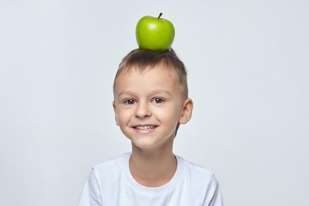 Na głowie słodkiego chłopca leży dojrzałe zielone jabłko