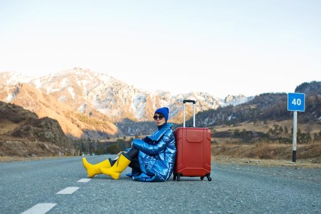Na górskiej drodze siedzi kobieta w niebieskiej kurtce i kapeluszu oraz jasnożółtych butach z czerwoną walizką, siedząca na górskich drogach