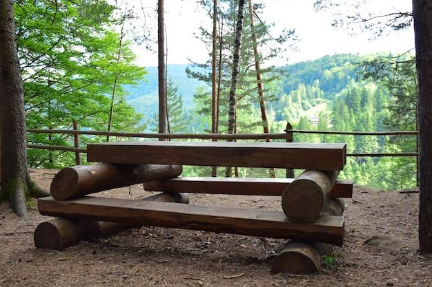 Na górze, w lesie, na tle drzew i kolejnej góry stoi pusta duża ławka i ręcznie robiony stół z bali.