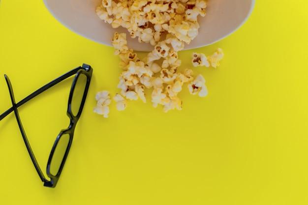 Na górze zdjęcia jest odwrócone białe pudełko po popcornu, z którego wysypuje się popcorn i d szklanki ...