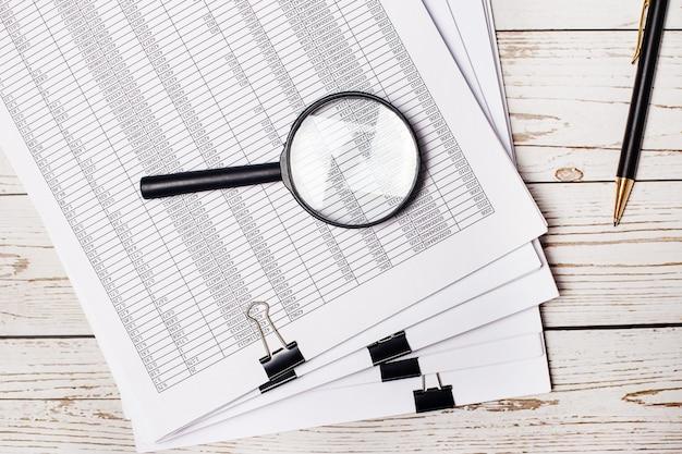 Na jasnej drewnianej powierzchni dokumenty i raporty, długopis i lupa