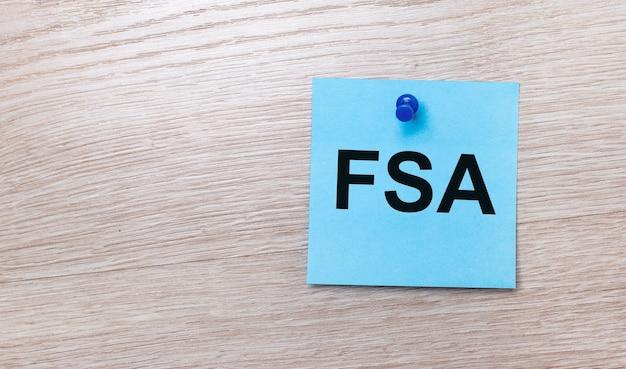 Na jasnej drewnianej powierzchni - jasnoniebieska kwadratowa naklejka z napisem fsa flexible spending account