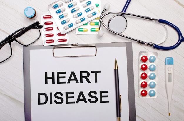 Na jasnej drewnianej powierzchni papier z napisem heart disease, stetoskop, kolorowe pigułki, okulary i długopis