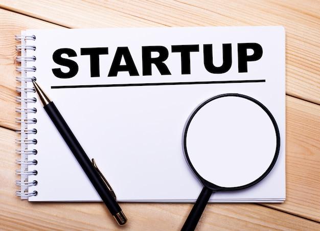 Na jasnej drewnianej powierzchni połóż długopis, lupę i zeszyt z napisem startup