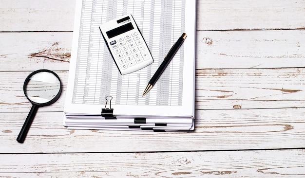 Na jasnej drewnianej powierzchni stos dokumentów, lupa, długopis i biały kalkulator