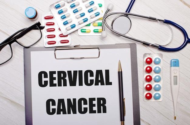 Na jasnej drewnianej ścianie papier z napisem cervical cancer, stetoskop, kolorowe pigułki, okulary i długopis. pojęcie medyczne