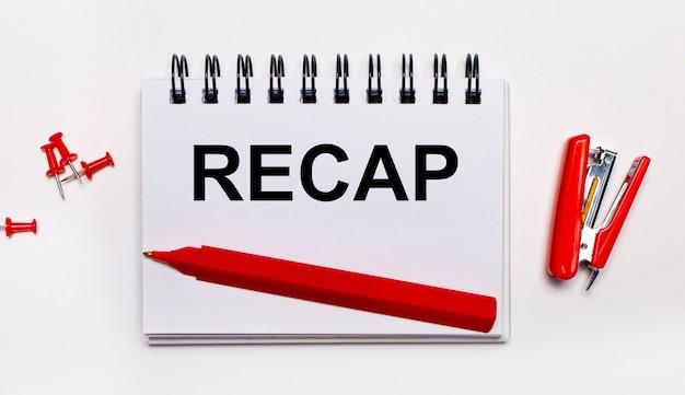 Na jasnej powierzchni czerwony długopis, czerwony zszywacz, czerwone spinacze i notes z napisem recap