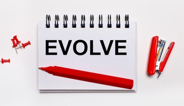 Na jasnej powierzchni czerwony długopis, czerwony zszywacz, czerwone spinacze i zeszyt z napisem evolve