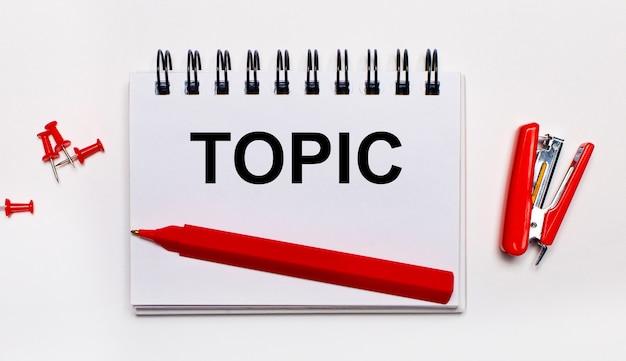 Na jasnej powierzchni czerwony długopis, czerwony zszywacz, czerwone spinacze i zeszyt z napisem topic