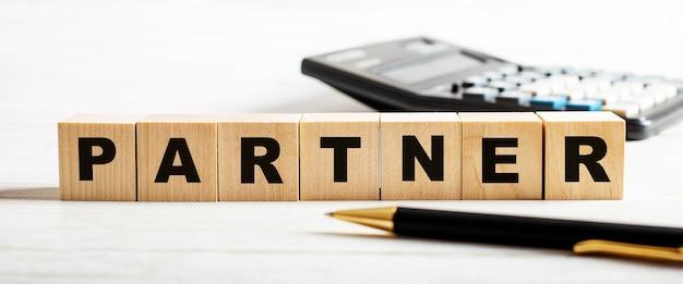 Na jasnej powierzchni długopis, kalkulator i drewniane kostki z napisem partner