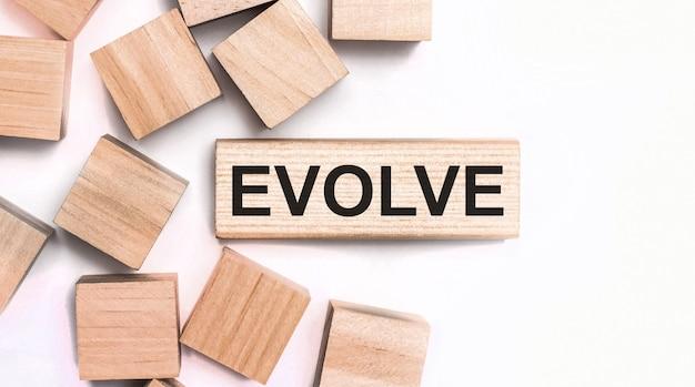 Na jasnej powierzchni drewniane kostki i drewniany klocek z napisem evolve. widok z góry