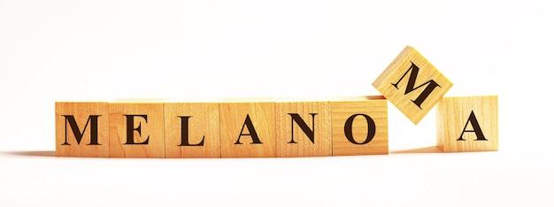 Na jasnej powierzchni drewniane kostki z napisem melanoma