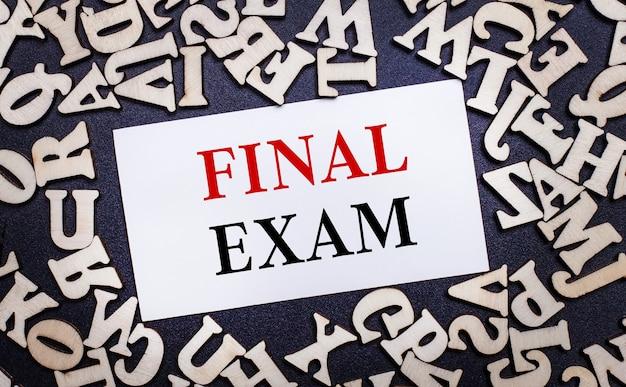 Na jasnej powierzchni drewniane litery alfabetu angielskiego, aw środku biała kartka z napisem final exam