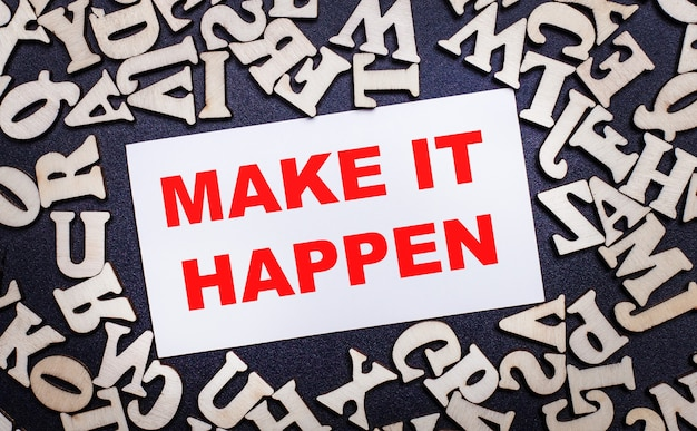 Na jasnej powierzchni drewniane litery alfabetu angielskiego, aw środku biała kartka z napisem make it happen