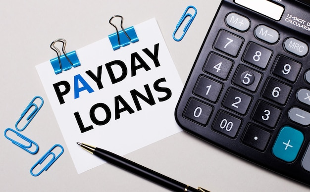 Na jasnej powierzchni kalkulator, długopis, niebieskie spinacze i kartka z napisem payday loans. widok z góry