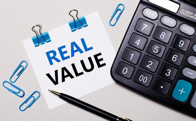 Na jasnej powierzchni kalkulator, długopis, niebieskie spinacze i kartka z napisem real value