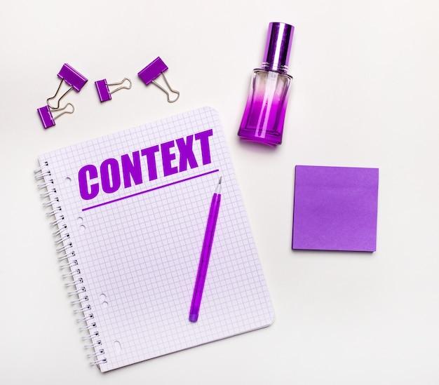 Na jasnej powierzchni - liliowy prezent, perfumy, liliowe dodatki biznesowe i notatnik z liliowym napisem context. leżał na płasko. koncepcja biznesowa kobiet
