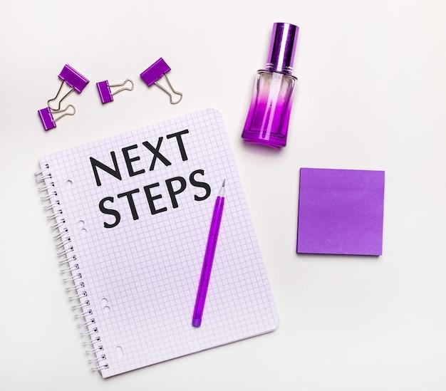 Na jasnej powierzchni - liliowy prezent, perfumy, liliowe dodatki biznesowe i notes z liliowym napisem następne kroki