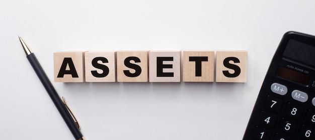 Na jasnej powierzchni między kalkulatorem a długopisem znajdują się drewniane kostki z napisem assets. koncepcja finansowa