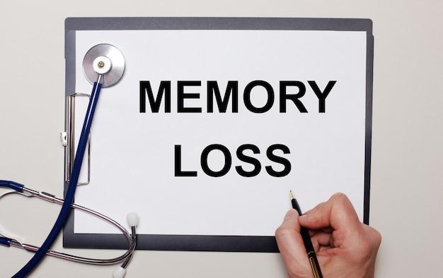 Na jasnej powierzchni stetoskop i kartka papieru, na której mężczyzna pisze utrata pamięci. pojęcie medyczne