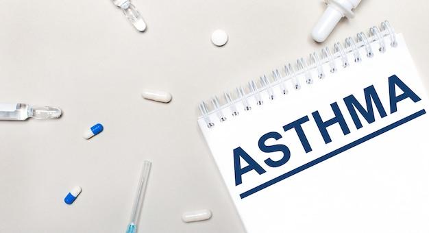 Na jasnej powierzchni strzykawka, stetoskop, fiolki z lekarstwem, ampułka i biały notes z napisem asthma