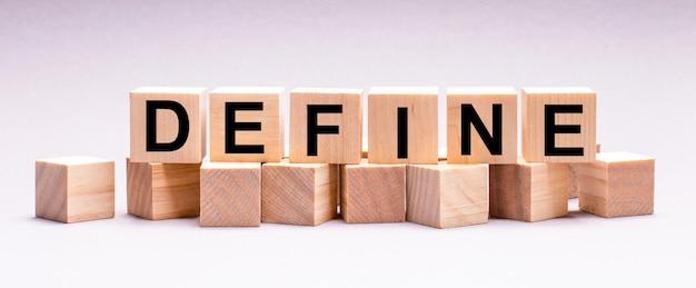 Na jasnej ścianie drewniane kostki z napisem define