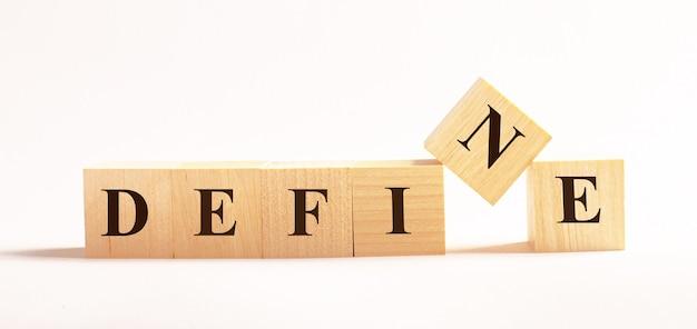 Na jasnej ścianie drewniane kostki z napisem define.