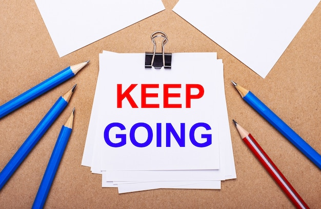 Na jasnobrązowym tle niebiesko-czerwone kredki i biały papier z napisem keep going
