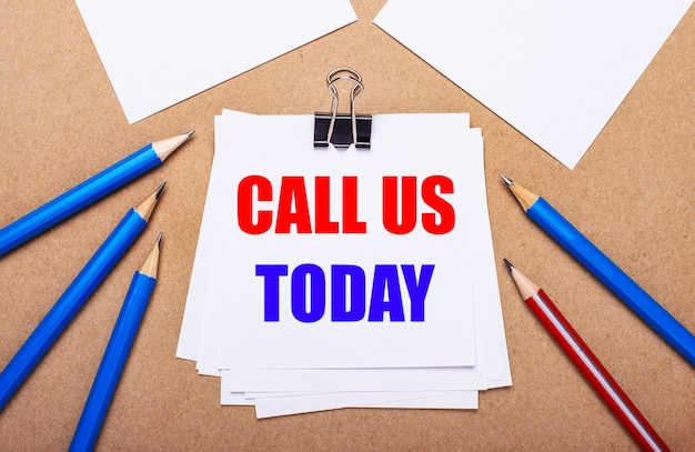 Na jasnobrązowym tle niebiesko-czerwone kredki i biały papier z napisem zadzwoń do nas dzisiaj