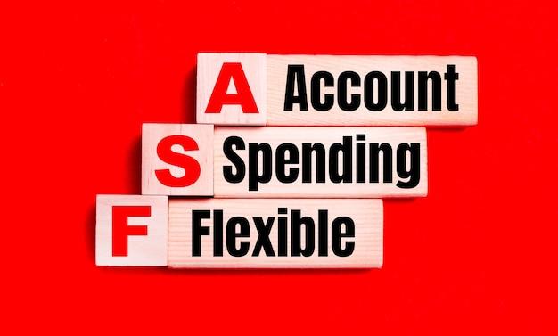 Na jasnoczerwonym tle jasne drewniane klocki i kostki z tekstem fsa flexible spending account.