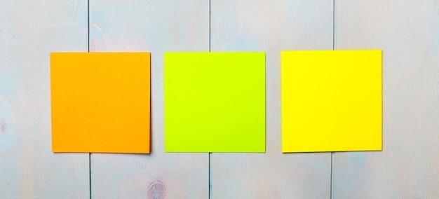 Na jasnoniebieskiej drewnianej powierzchni znajdują się trzy kolorowe naklejki do pisania. szablon. skopiuj miejsce