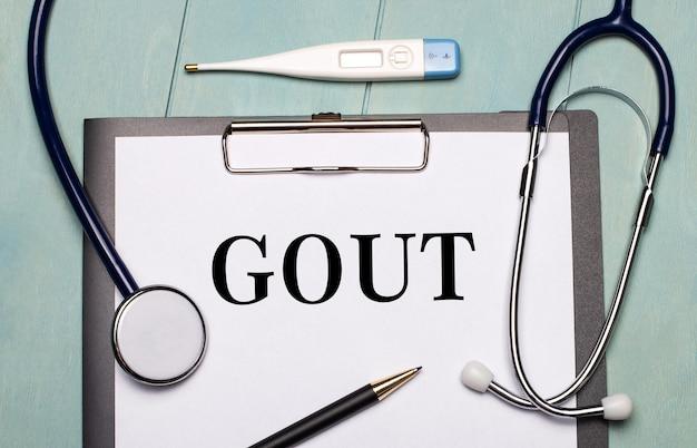 Na jasnoniebieskiej drewnianej powierzchni znajduje się papier z napisem gout, stetoskop, termometr elektroniczny i długopis. pojęcie medyczne