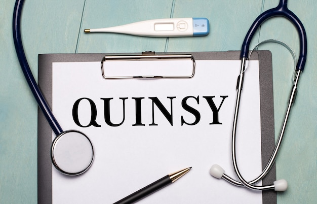 Na jasnoniebieskiej drewnianej powierzchni znajduje się papier z napisem quinsy, stetoskop, termometr elektroniczny i długopis