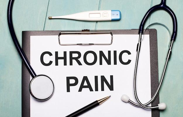 Na jasnoniebieskiej drewnianej ścianie znajduje się papier z napisem ból przewlekły, stetoskop, termometr elektroniczny i długopis. pojęcie medyczne